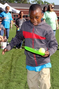 Kendarius Thomas, 8, a Bolton-Edwards Elementary student, plays a relay game with a Frisbee and tennis ball.