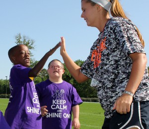 Henry Hankins, 10, Gary Road Intermediate School, gives a high five to Hinds Community College student Molli Douglas, a Raymond Campus softball player. In the background is Tyler Archibald, 11.