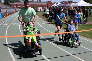 In the grand finale of the field day, Byram Middle coach Robert Pittman, a Hinds alumnus, pushes Brannon Martin while volunteer Mallory Coleman pushes Rachel Myers, 8, in the wheel chair race.