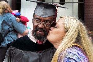 Roy Harness, left, poses for a photo following commencement exercises at Cain-Cochran Hall May 15. Harness, of Jackson, earned an Associate's of Arts in drafting and design and plans to pursue a bachelor's from Jackson State University. Pictured giving Harness a celebratory kiss is Barbara Cheney, right.