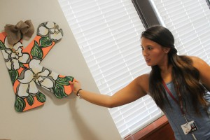 Kasey Kimery of Pearl, a sophomore studying dental hygiene at Hinds Community College, hangs wall decorations in her room in Allen-Dukes-Whitaker Residence Hall on the Raymond Campus on Monday, Aug. 3. Kimery, a captain in the Hi-Steppers, was among students moving in early to participate in band camp.