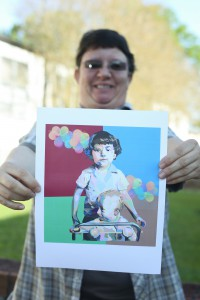 """Sol Dominguez holds a copy of her piece, """"My Brother and Me,"""" which was awarded first place in the graphic design category at the Mississippi Community & Junior College Art Instructor's Association State Art Competition earlier this semester. (April Garon/Hinds Community College)"""