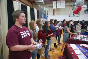 Arryn Peterson, left foreground, clutches a tee shirt after signing a commitment with Hinds Community College during a signing day event May 6 at Pisgah High School. (April Garon/Hinds Community College)