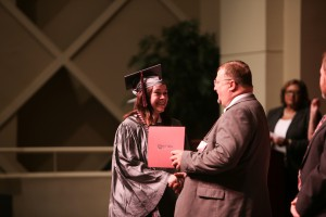 Ashley Clark, left, shakes hands with Dr. Chad Stocks, vice president for Workforce Development at Hinds Community College, during a ceremony at Cain-Cochran Hall on the college's Raymond Campus on June 23 recognizing those who earned their GED certificate in the recent academic term. (April Garon/Hinds Community College)