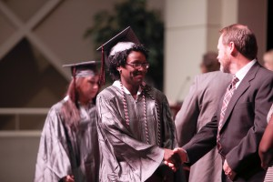 I'Esha Granderson, left foreground, shakes hands with David Creel, district Director of Manufacturing Training at Hinds Community College, as she walks across the stage at Cain-Cochran Hall on the college's Raymond Campus to accept her GED certificate on Thursday, June 23, 2016. (April Garon/Hinds Community College)