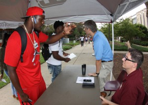 Godey Coleus, left foreground, a freshman student from Tampa, Fla., stops for help finding a class on the first day of the Fall 2016 semester at Hinds Community College's Raymond Campus. At the table are recruiters Shane Brown, foreground, and Chris Evans. (Tammi Bowles/Hinds Community College)