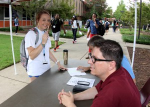 Taylor Conway, left, of Clinton, stops for help finding a class on the first day of the Fall 2016 semester at Hinds Community College's Raymond Campus. Seated at the table are recruiters Shane Brown, foreground, and Chris Evans. (Tammi Bowles/Hinds Community College)