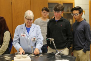 Hinds Community College chemistry instructor Lou Ann Williams sets up a science demonstration while Copiah Academy seniors Caleb Phillips and Noah Chapa, both of Crystal Springs, watch.