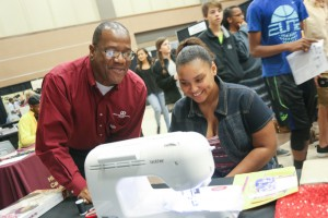 Curtis Gore, instructor at the Utica Campus, gives Tyran Crain, a Puckett eighth-grader, a quick lesson on using a Brother computerized sewing machine. She was among more than 1,200 area students who visited the Hinds Community College Career Exploration Day on Nov. 8.