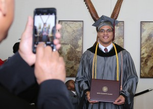 Texas native Ivan Muniz of Clinton plans to return to Texas for a job in a hospital emergency room after receiving his Associate Degree in Nursing from Hinds Community College on Dec. 16. He is standing in front of a carved eagle at the Muse Center on the Rankin Campus.