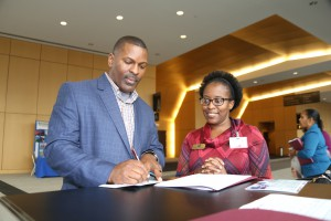 Angela Hayes, district WIN Center Education Coordinator, looks on as Jimmie Coins, human resource specialist with Atmos Energy , signs up to recognize the ACT Work Ready Community effort Jan. 18 at the Jackson Convention Complex. (Hinds Community College/April Garon)