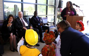 Dr. Mary Ann Greene, seated at left, interacts with children from the Early Childhood Education Technology program at Hinds Community College Jackson Campus-Academic/Technical Center during a program March 31 to name the program's building in her honor. Also seated are Hinds President Dr. Clyde Muse, center, and JATC Dean Leroy Levy. At the podium is Dr. Ericka Davis, who succeeded Greene as program director. Standing with the children is Carolyn Watkins, an assistant in the Early Childhood Education Laboratory. (Hinds Community College/Tammi Bowles)