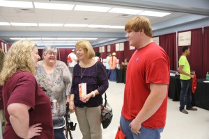 Ferran Parker, right, a senior at Warren Central High School, speaks with Dr. Sarah Nichols, left, at College Night at Hinds Community College Vicksburg-Warren Campus April 18. In the background are Donna Tingle, his aunt, and Jenny Parker, his mother. (Hinds Community College/April Garon)