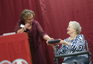 Bobbie Anderson, seated, retired dean of Hinds Community College Jackson Campus-Nursing/Allied Health Center, receives a personalized medallion from Jackie Granberry, executive director of the Hinds Community College Foundation, during a reunion Sept. 21 of former deans and instructors at the facility. (Hinds Community College/April Garon)