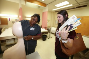 Lekishi Davis, a second-year nursing student at Hinds Community College, demonstrates usage of a nasogastric tube on a cross-section model at the fall 2017 Nursing Showcase on Sept. 5 at Hinds Community College Jackson Campus-Nursing/Allied Health Center. (Hinds Community College/April Garon)