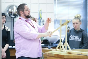 Dr. Carl DeWitt, physics instructor at Hinds Community College Rankin Campus, holds a small rubber pumpkin he used as the projectile for a small catapult during this year's Honors Day event held on campus Oct. 20. (Hinds Community College/April Garon)