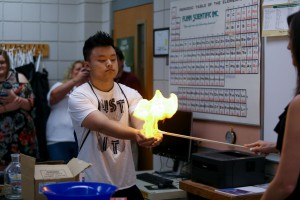 Jason Lin, of Brandon High School, holds flaming soap suds in his hands as part of an experiment at Honors Day at Hinds Community College Rankin Campus Oct. 20. (Hinds Community College/April Garon)