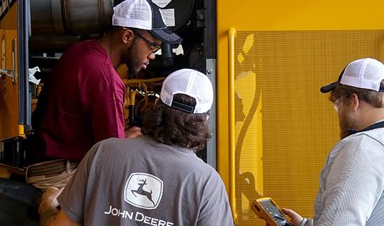 three students working on diesel engine