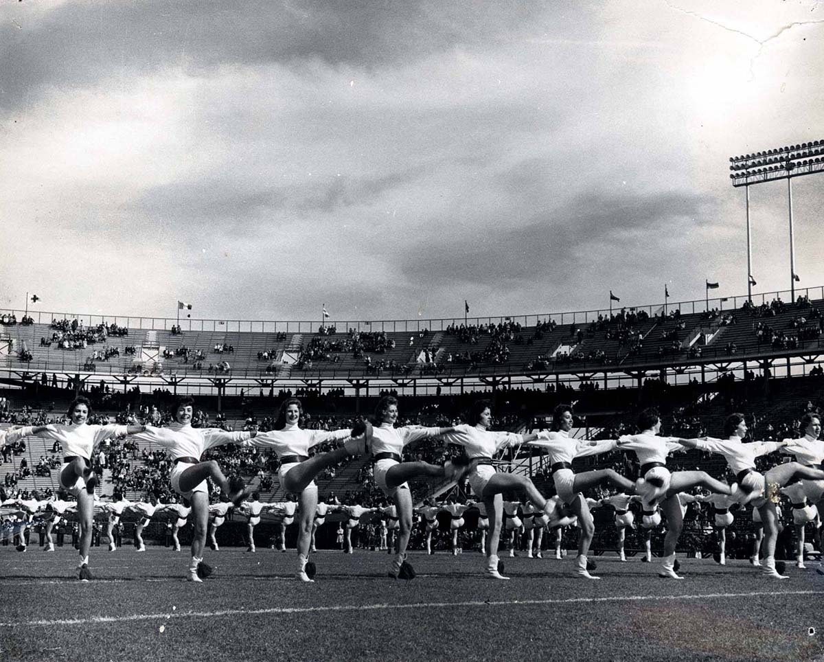 black and white photo of college dance line on football field