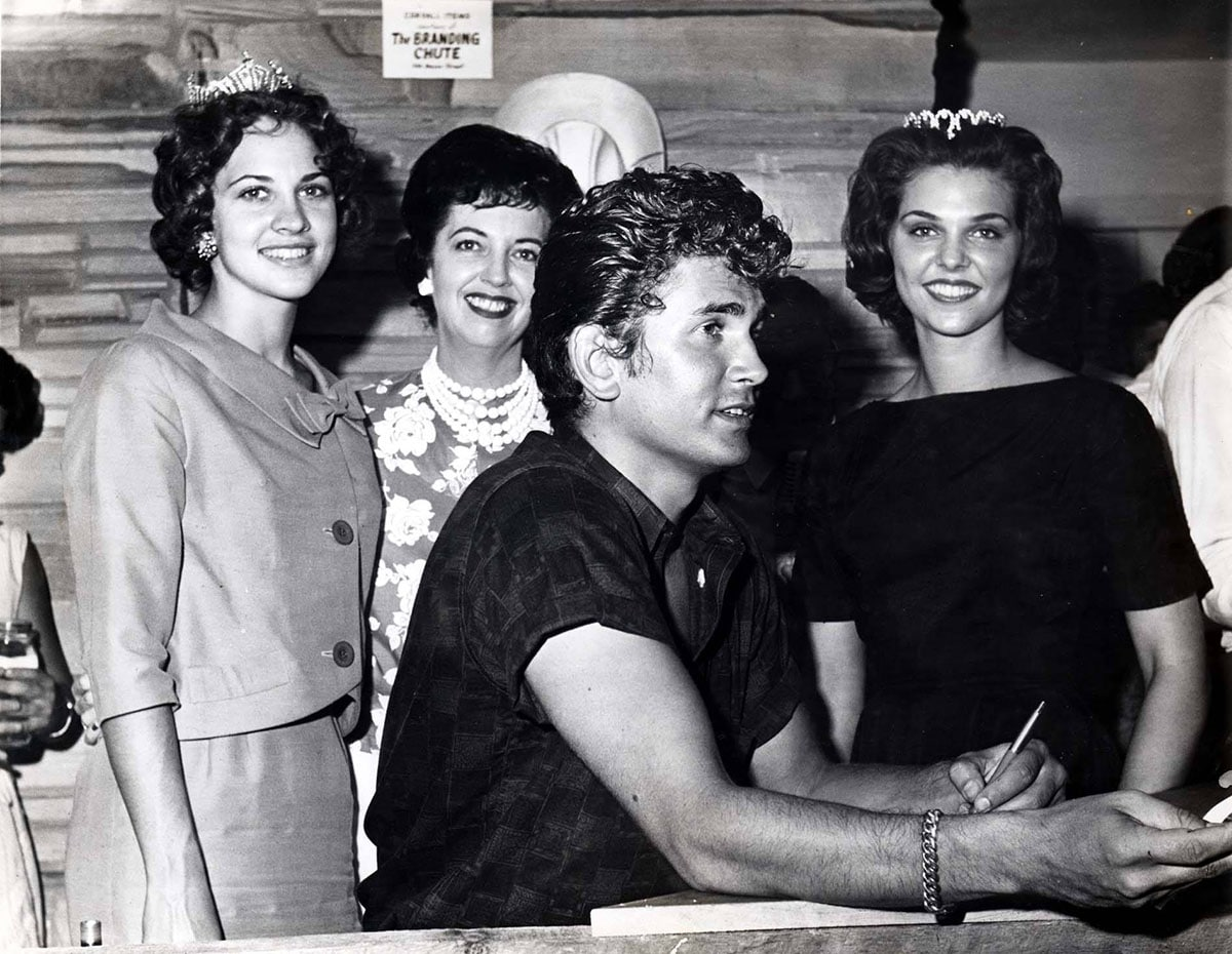 old black and white photo of young man with three young women behind him