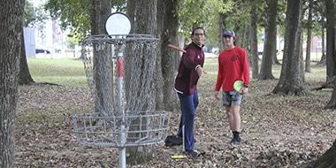 students playing disc golf scramble