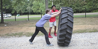 female student flipping over a large tire