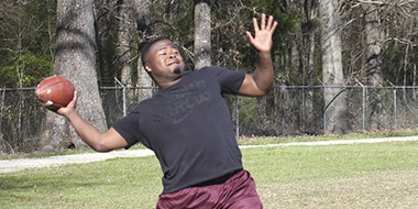 young black male leaning back to pass a football