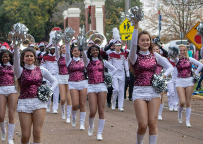 hi-steppers in maroon and white uniforms marching in parade