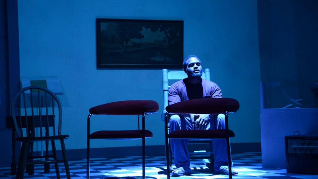 actor on stage in blue light