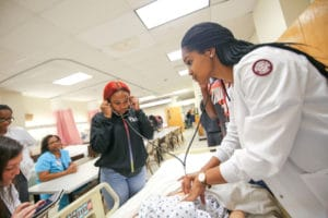 student listens for a heartbeat in a manikin