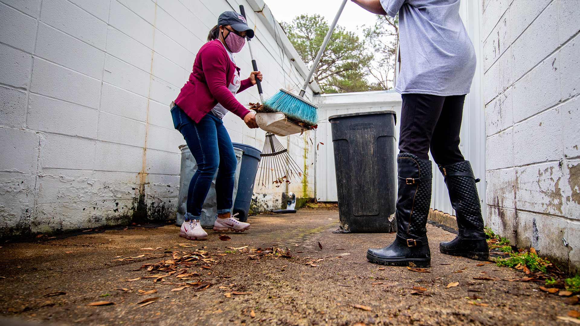 Christy Laster, left, and Cassandra Ellis work together to clear an area of leaves and pine needles.